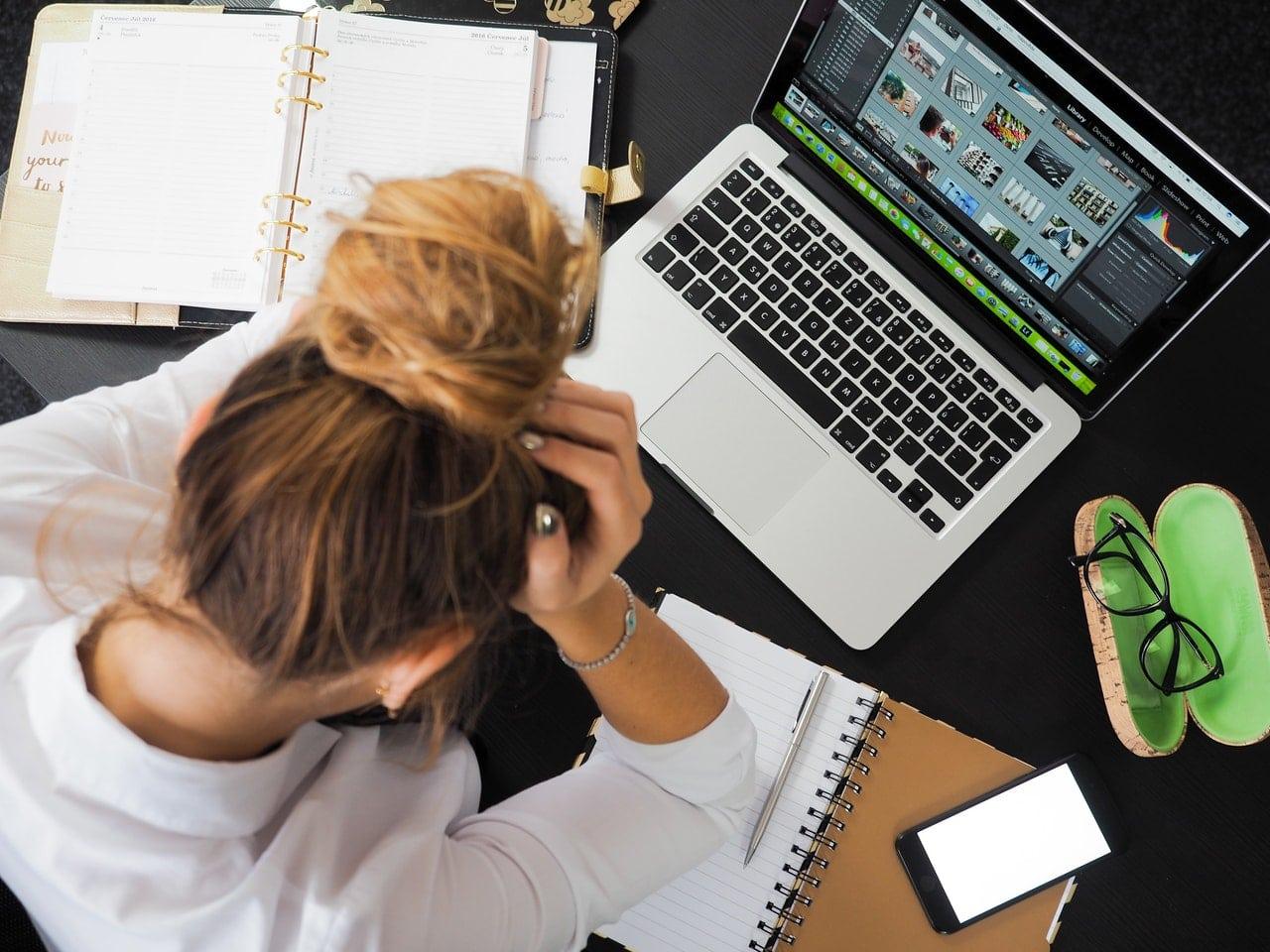 Une jeune femme stressée travaillant devant son ordinateur