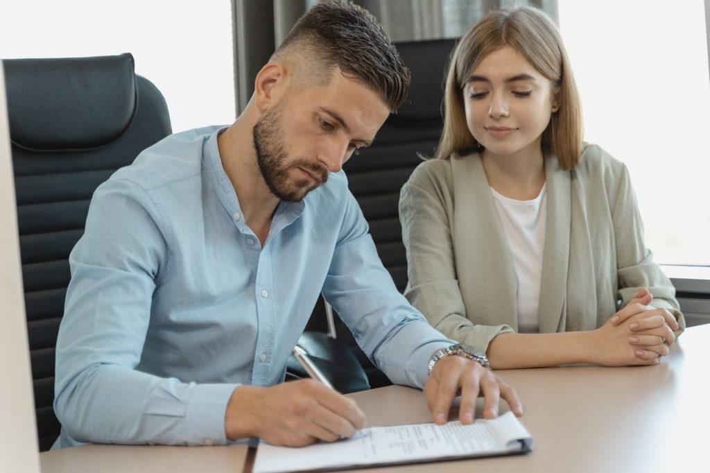 homme qui signe un contrat en étant assis à côté d'une femme
